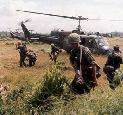 Troops disembark from a helicopter during the Vietnam War