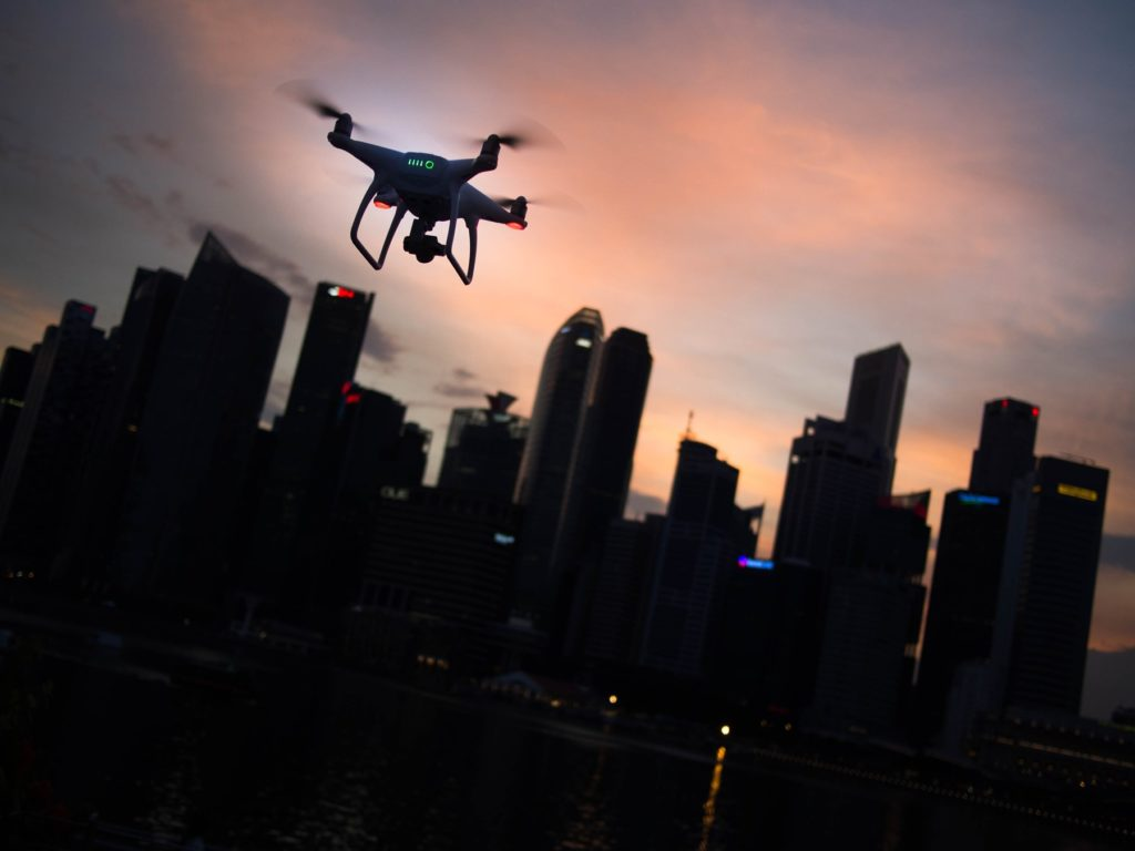 Drone over city skyline silhouette. Photo by Goh Rhy Yan on Unsplash