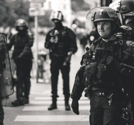 Greyscale armed French police. Photo by ev on Unsplash