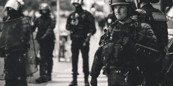 Greyscale armed French police. Photo byevonUnsplash
